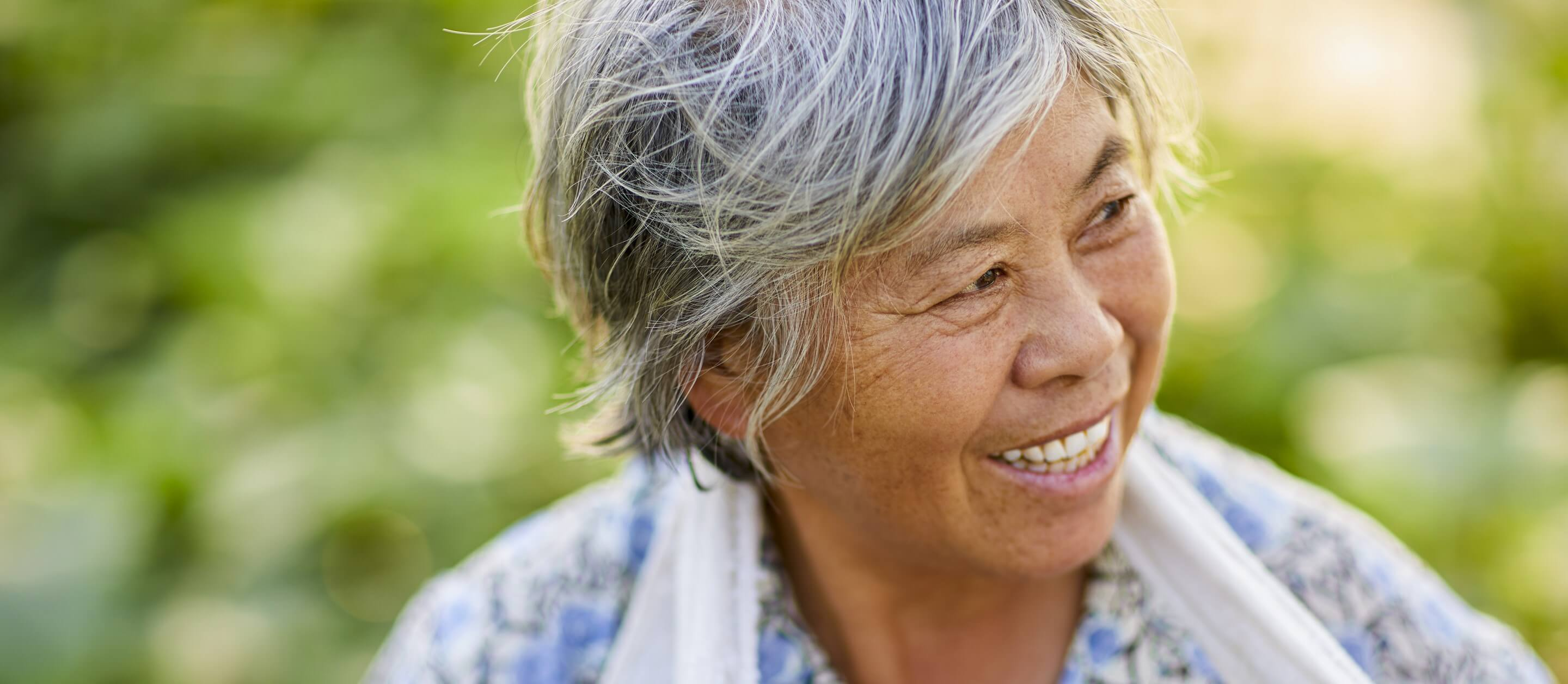 Mature Asian woman with grey hair smiling and looking to her left with bright green leaves in the background