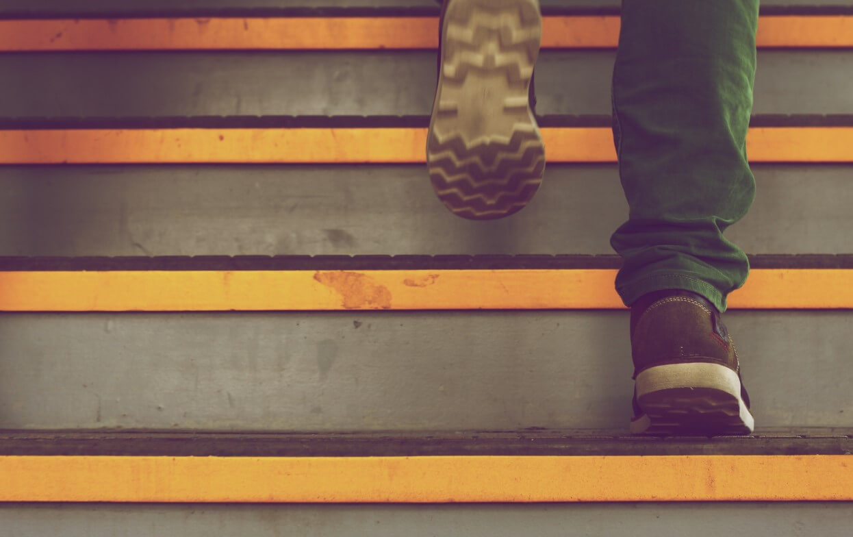 Close-up of a man's feet walking up stairs with bright yellow strips for visability