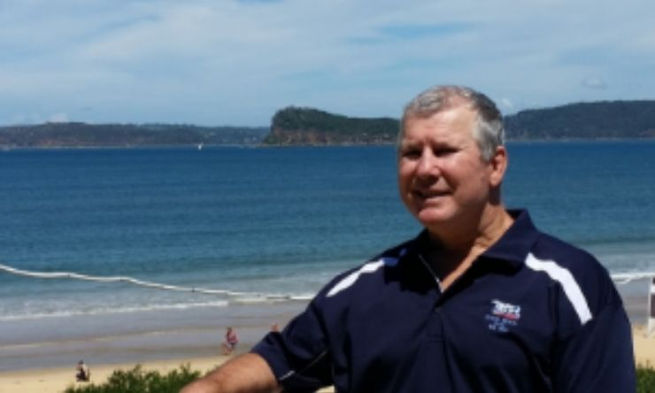 Image of man standing with beach in the background