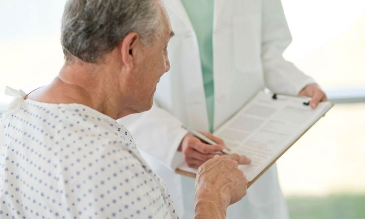 Male patient in hospital bed signing document
