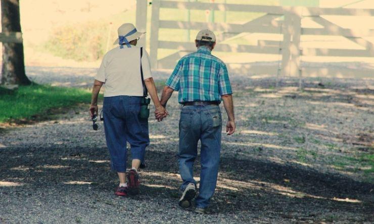 Older couple walking into farm paddock