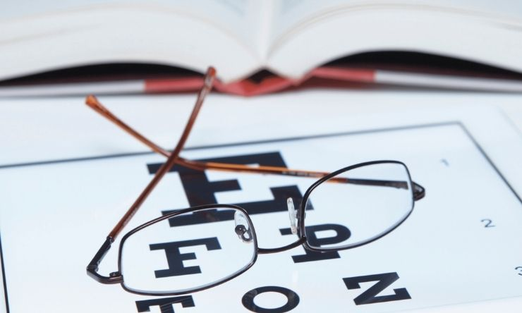 Image of glasses resting on vision text