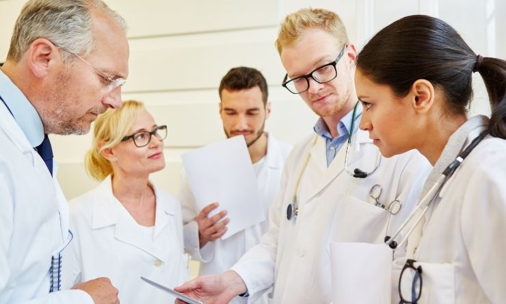 Group of physicians standing having a discussion with a patient chart