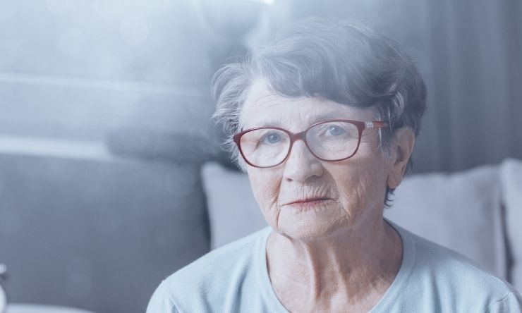 80 year old woman with grey hair and red rimmed glasses