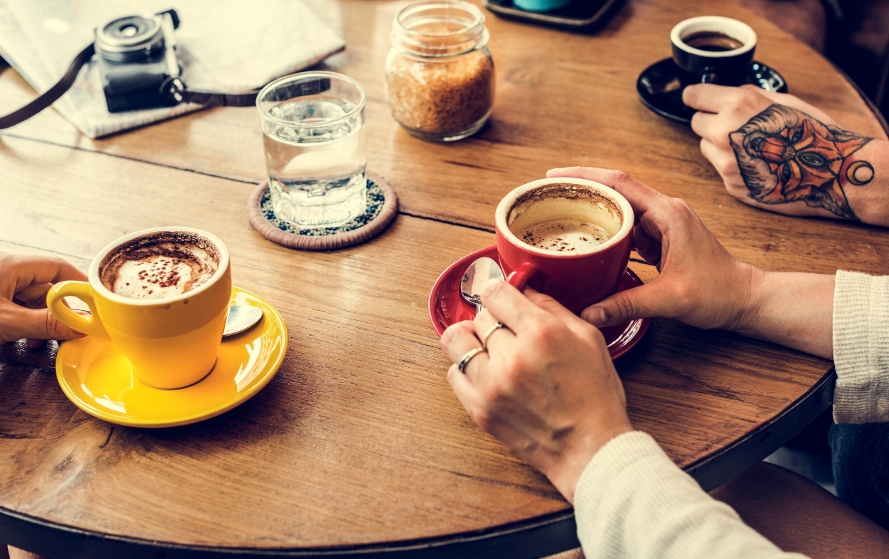 hands holding coffee cups around table in cafe