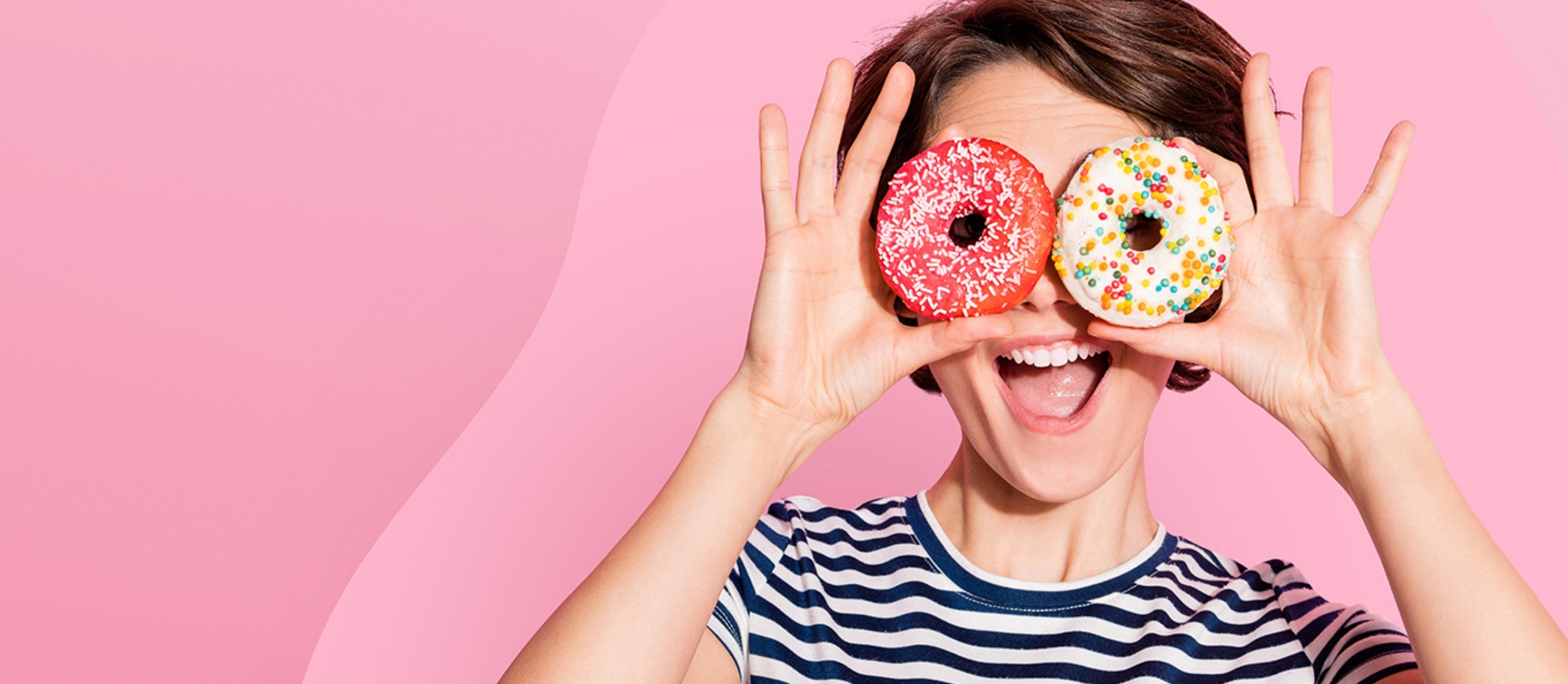 Smiling young woman in striped t-shirt holding iced doughnuts over eyes