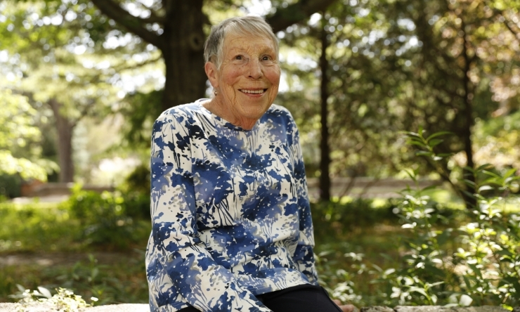 Image of smiling older woman in floral blouse sitting on garden wall with trees in background