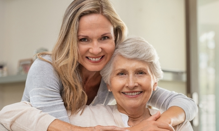 Woman in 70s sitting on couch being hugged from behind by younger woman, both happy and smiling
