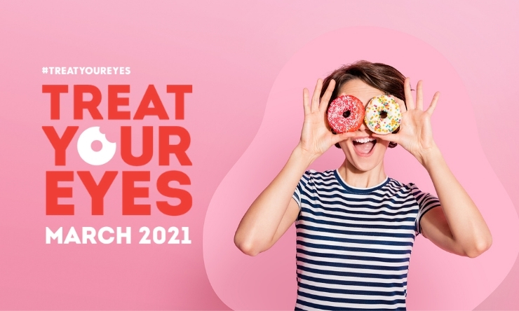 Image of woman holding iced donuts over her eyes and smiling
