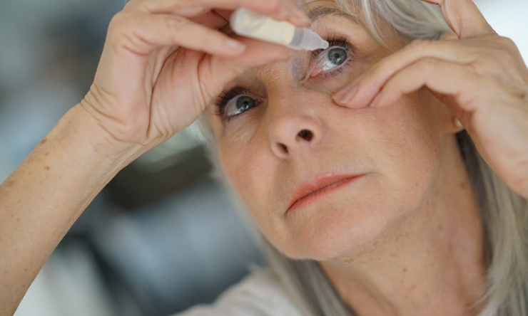 Image of middle aged blonde haired woman applying eye drops to her eyes
