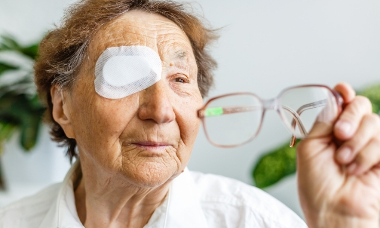 Image of older woman with post surgery eye patch, holding up her reading glasses