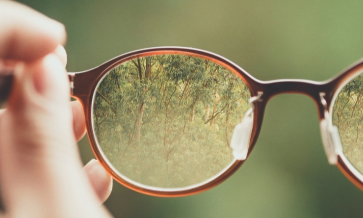 Image of glasses looking into a green background
