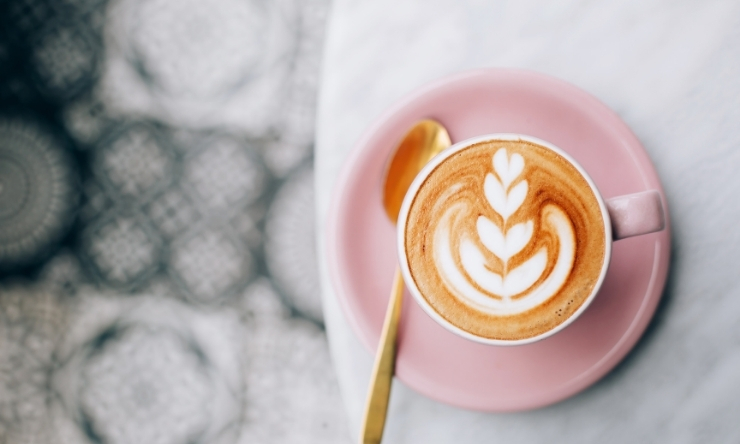 Image of barista made flat white coffee in pale pink cup and saucer sitting on table