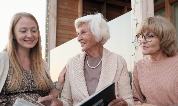 Image of a grandmother, mother, and daughter looking through family albums.
