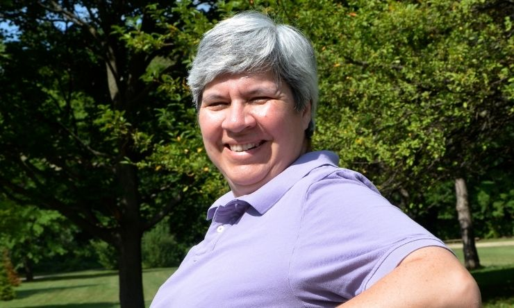 Image of woman with grey hair, wearing purple polo shirt sitting on park bench