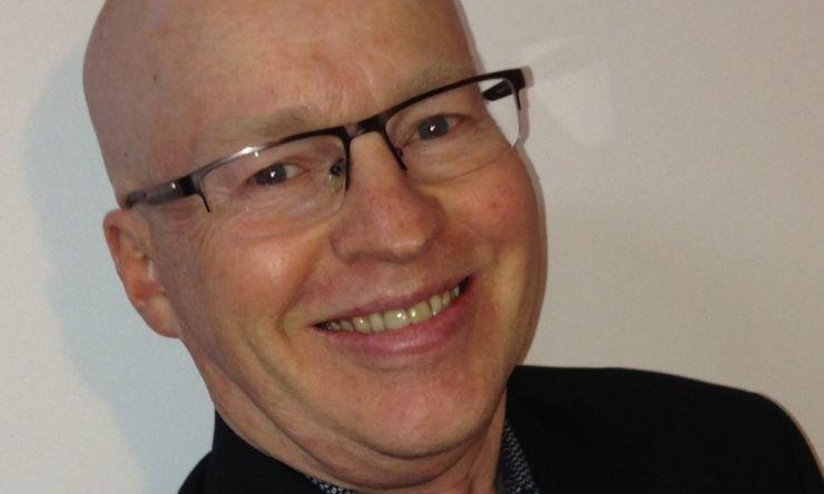 Close up image of bald man wearing glasses