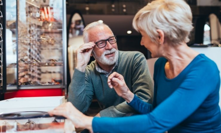 Image of older man and woman trying on glasses at an optometrist