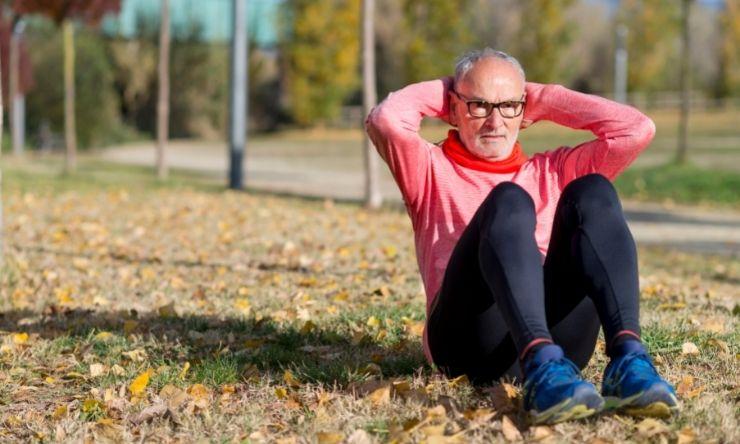 image of older man in park doing sit ups