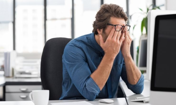 Image of stressed looking man at computer desk