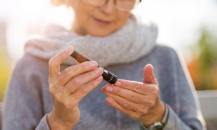 Image of woman applying a blood sugar test to finger