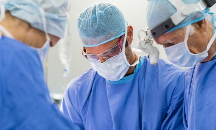 Image of three surgeons in operating theatre