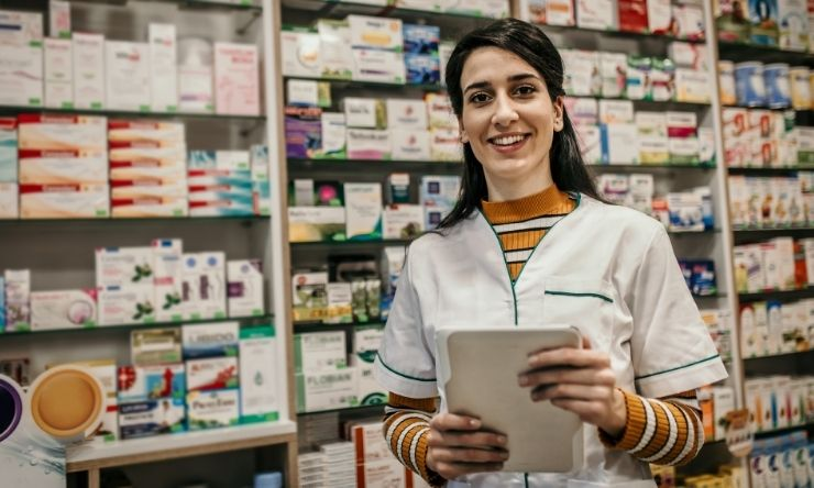 Image of smiling pharmacist standing in front of shelves with medication