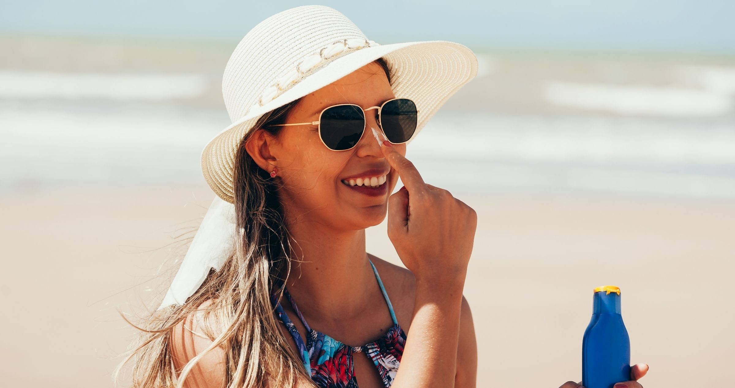 Lady at beach wearing sunglasses, hat and sunscreen
