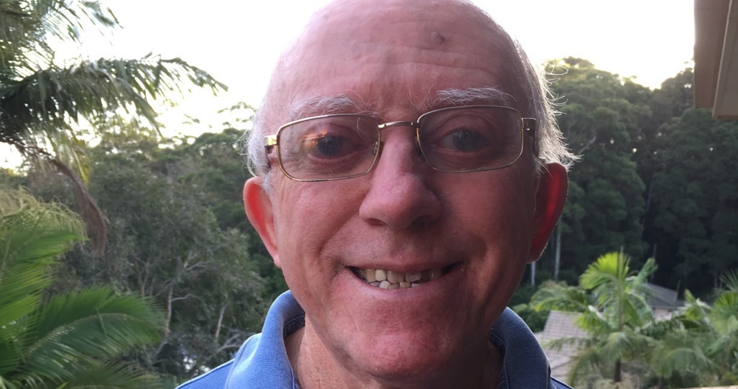 Image of smiling man with glasses and blue polo shirt with tropical trees in background