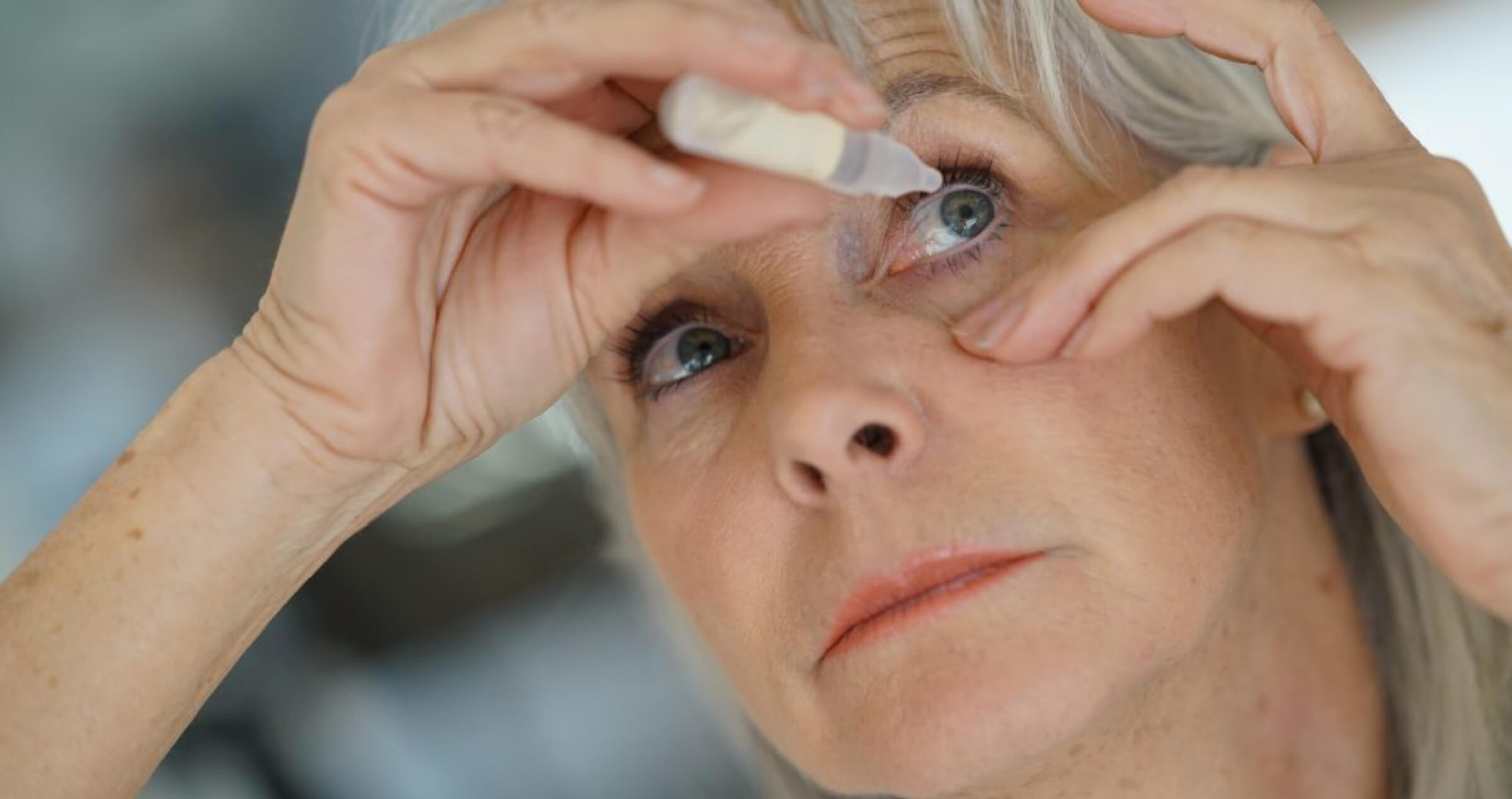 Image of middle aged blonde haired woman applying eye drops to her wyes