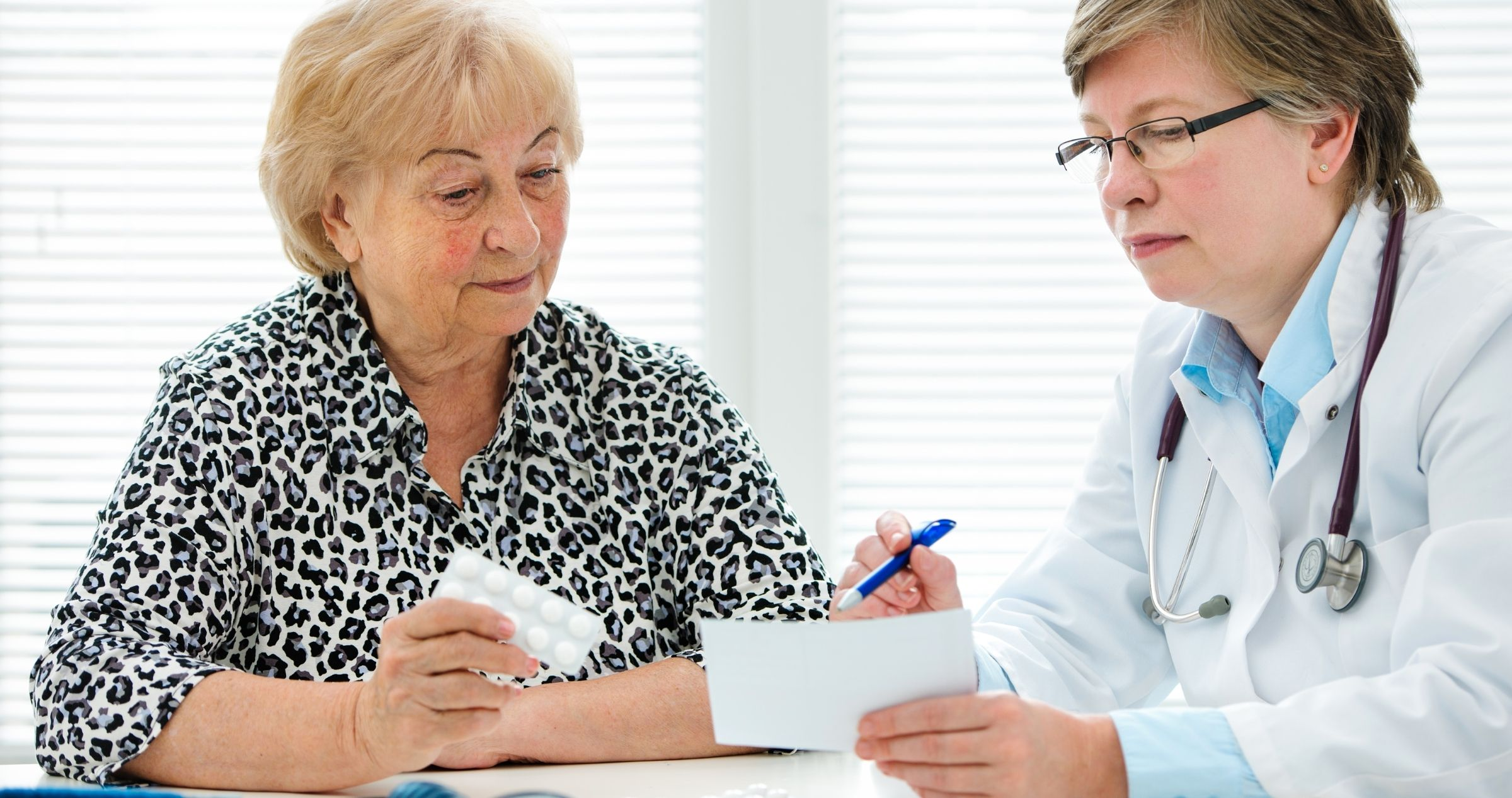 Patient sitting at desk with doctor