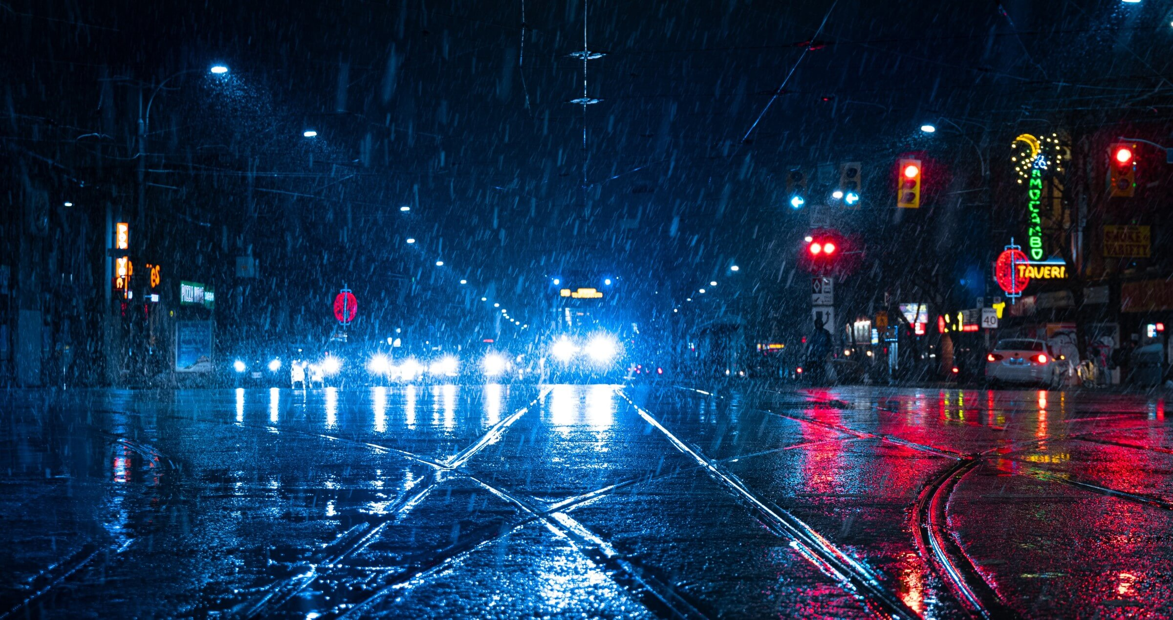 A busy city intersection on a dark and raining night with lights reflecting off the road