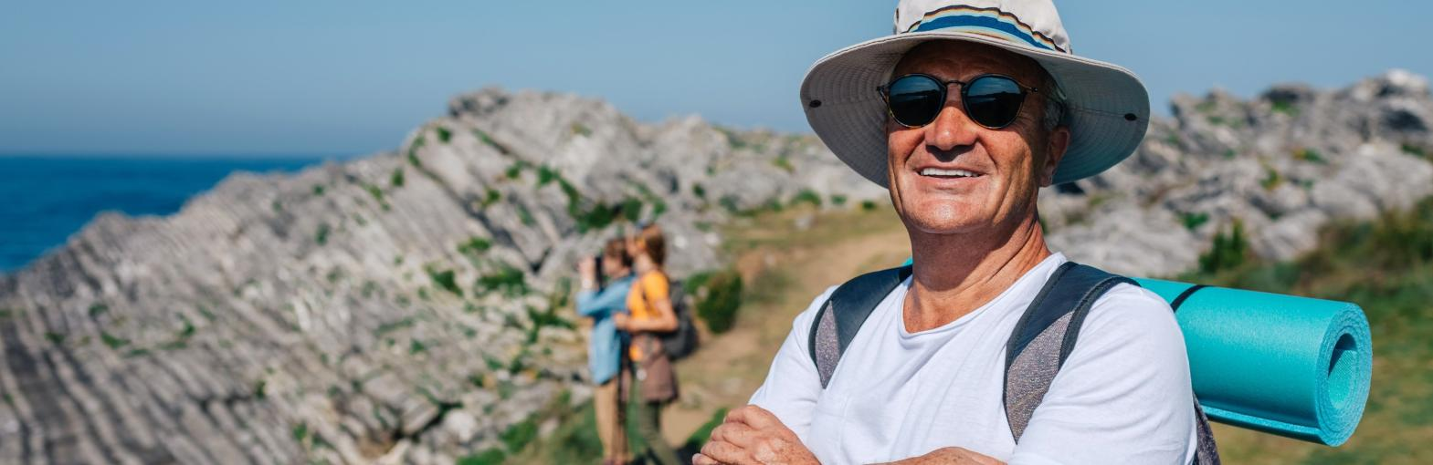 Happy senior man trekking along a seaside track smiling at the camera