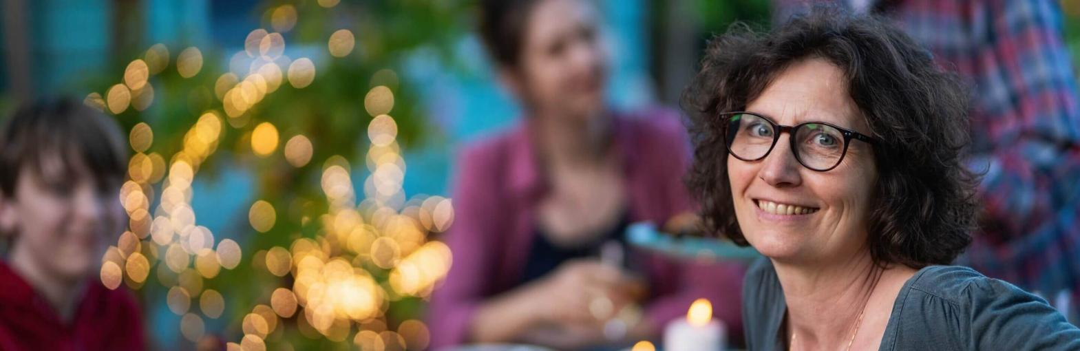 Woman eating outside at night with her family