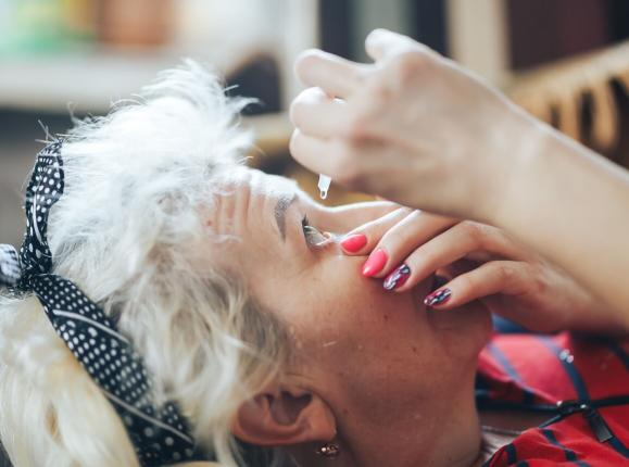 Woman with grey hair instilling glaucoma eye drops at home