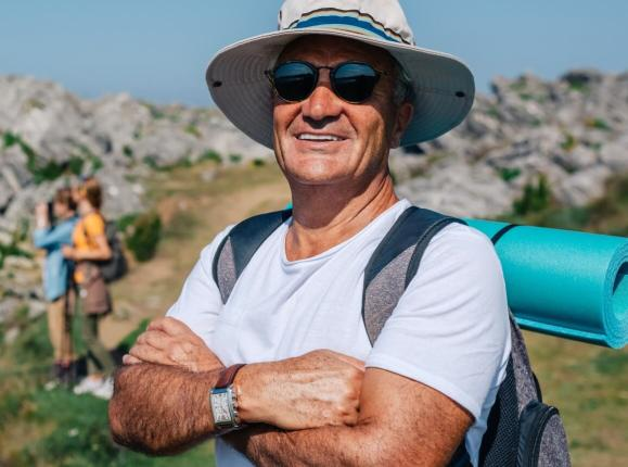 Happy, healthy looking 50 year old man trekking along a seaside cliff.