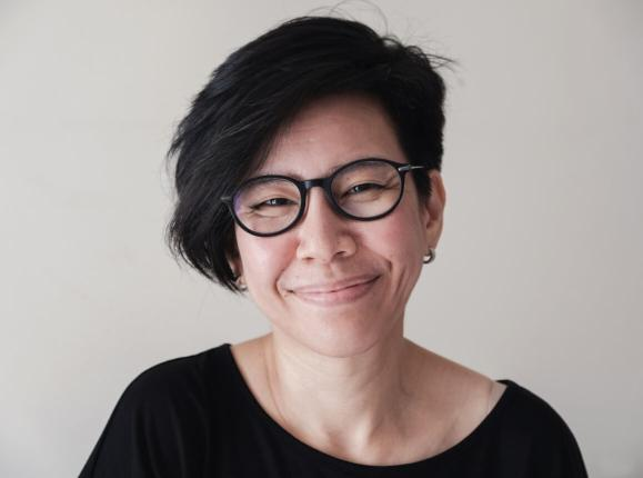 Happy natural looking Asian woman with black rimmed glasses smiling at the camera