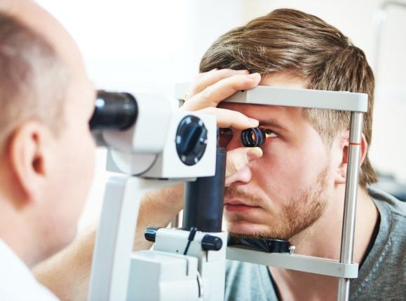 Male optometrist examining a mans eye using gonioscopy