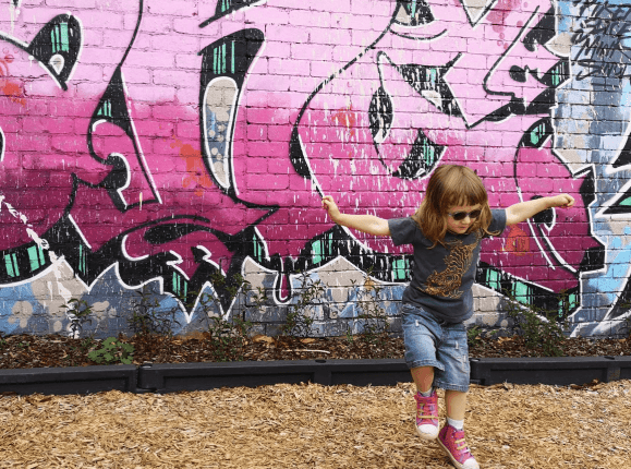 3 year old girl dancing in front of graffitied wall