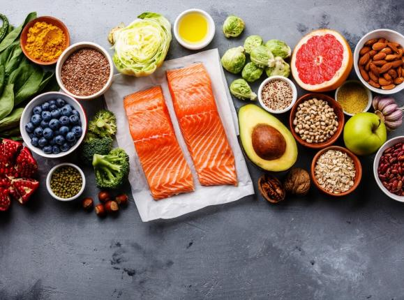 A selection of healthy foods including salmon, avocado, leafy greens, berries, citrus, nuts and seeds