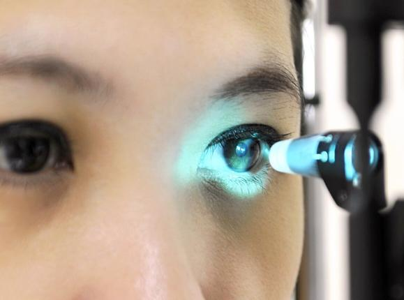 A close-up of a young Asian woman's eye being checked using Applanation Tonometry to measure eye pressure