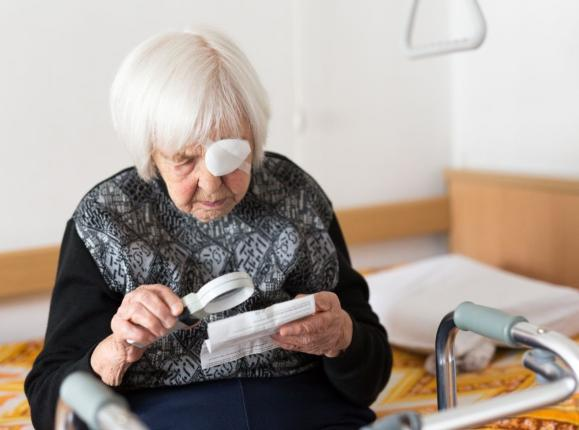 Elderly woman reading newspaper with magnifier and a patch on one eye