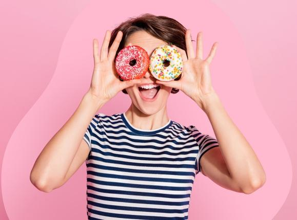 Young woman holding up doughnuts over her eyes and smiling
