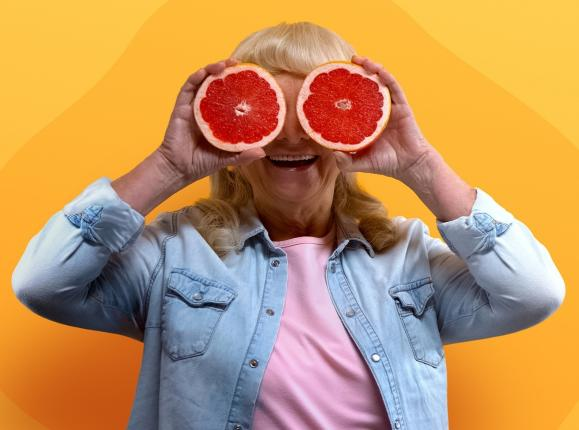 Woman in denim jacket and pink t shirt holding up grapefruit halves over her eyes