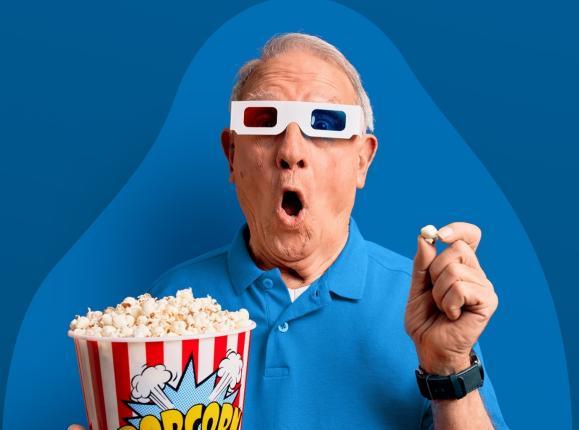 Surprised older gentleman holding popcorn wearing 3D glasses