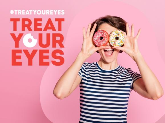 Image of young woman in black and white striped t-shirt, smiling and holding donuts over her eyes, with a pink background and red type stating 'Treat Your Eyes'