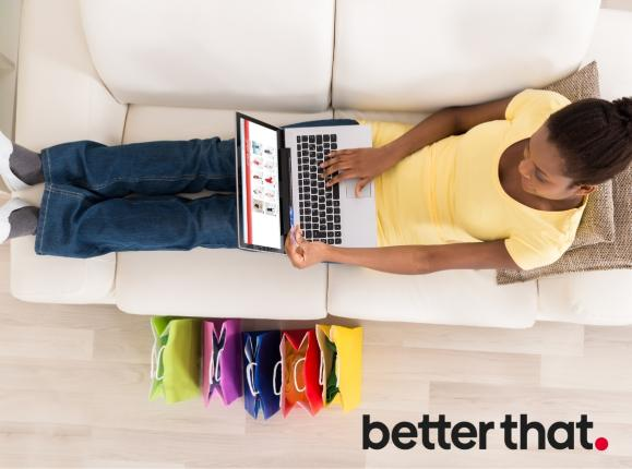 image of young woman online shopping, reclining on couch