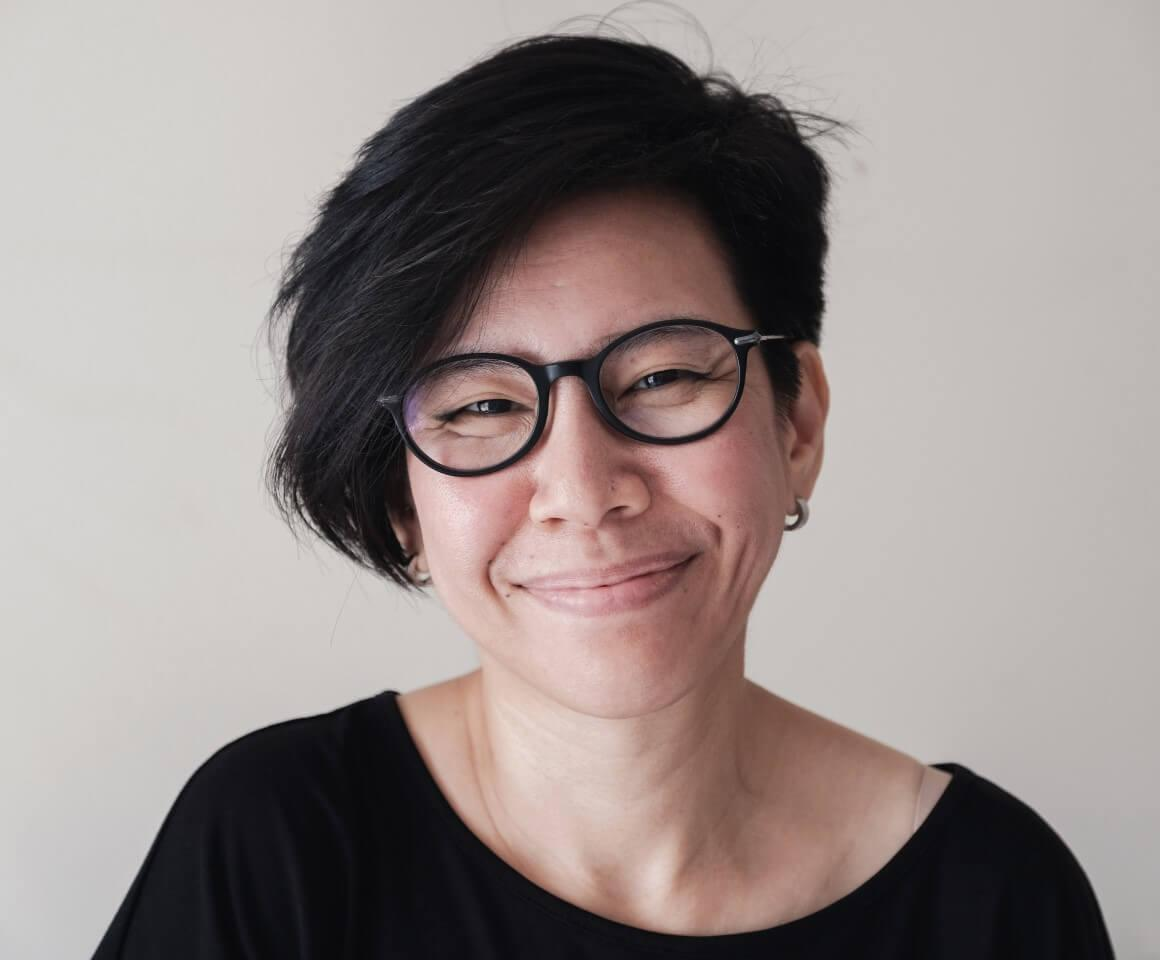 Portrait of happy, natural looking middle aged Asian woman wearing glasses and smiling at camera