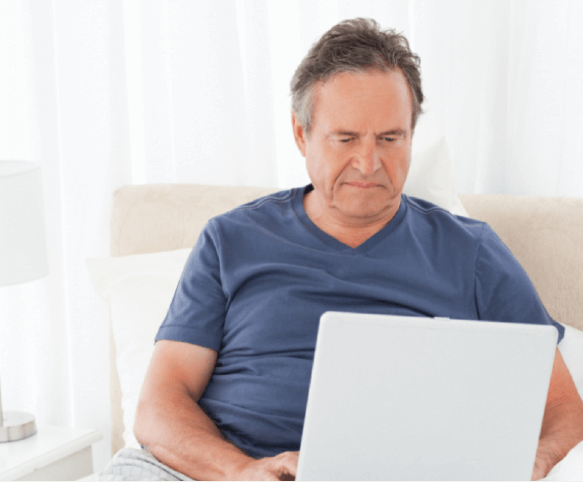 Middle aged man sitting in bed searching on his laptop