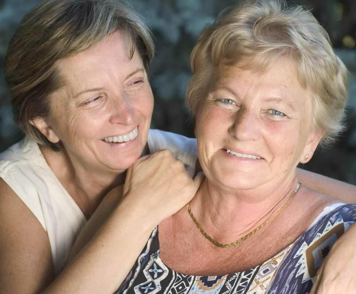 Image of two Caucasian women. Woman on the left is has her arm around the shoulder of the woman on the right and is looking at her smiling. Woman on the right is looking a the camera and smiling.