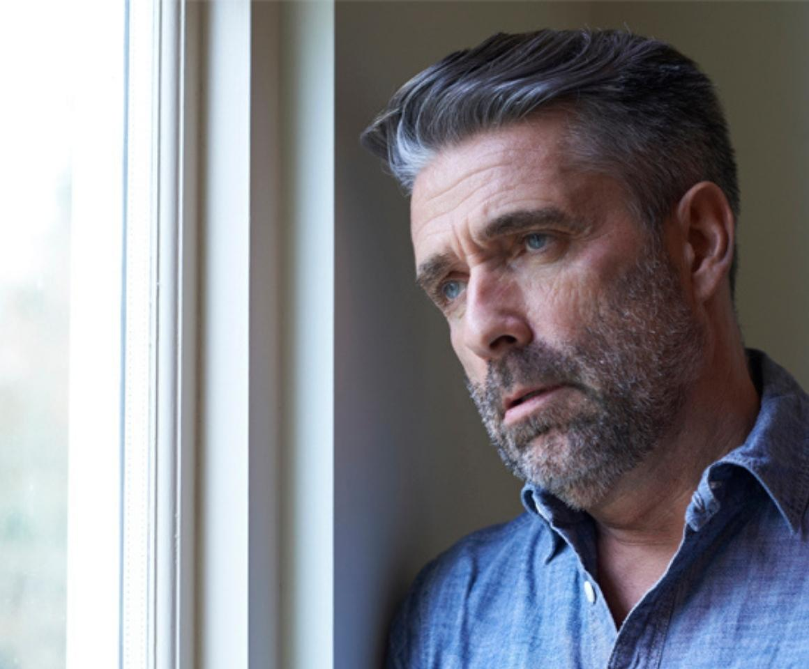 middle aged man staring out window looking concerned